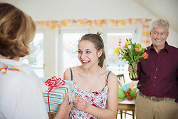 Granddaughter handover present to her grandmother while grandfather waiting with bouquet