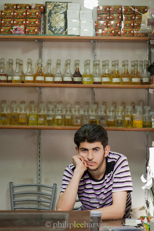 A man selling perfumes and fragrances at his stall in a souq in the Old City in Damascus, Syria