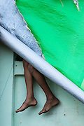 Legs and feet hanging from green tarp at Bahozagyi, Market, Taungoo