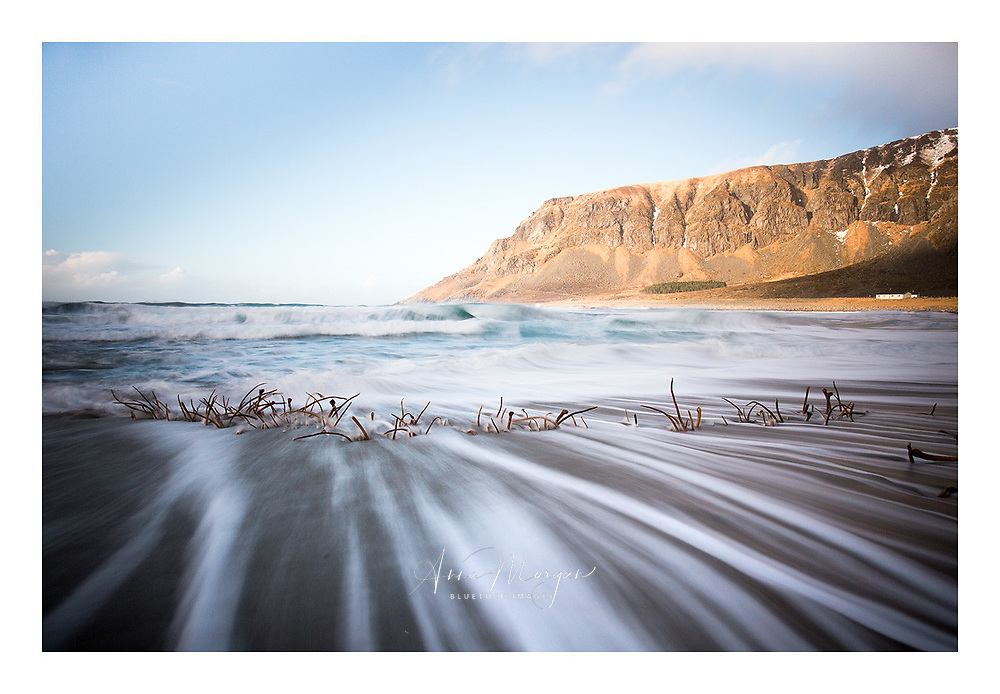 Long exposure showing wave movement streaking down beach around seaweed on Unstad beach, Lofoten, Norway
