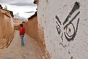 A woman in being observed by a graffiti in one street of Cuzco.