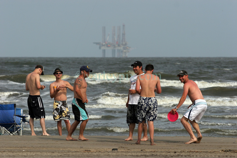 13 May 2010. Grand Isle, Lafourche Parish, Louisiana. <br /> Tourists enjoy the afternoon on the beach in the shadow of a drilling rig. Oil is now landing on the beaches of Jefferson and Lafourche parishes to the west of the Mississippi River outlet. Oil from the Deepwater Horizon catastrophe is evading booms laid out to stop it thanks in part to the dispersants which means the oil travels at every depth of the Gulf. <br /> Photo credit; Charlie Varley/varleypix.com