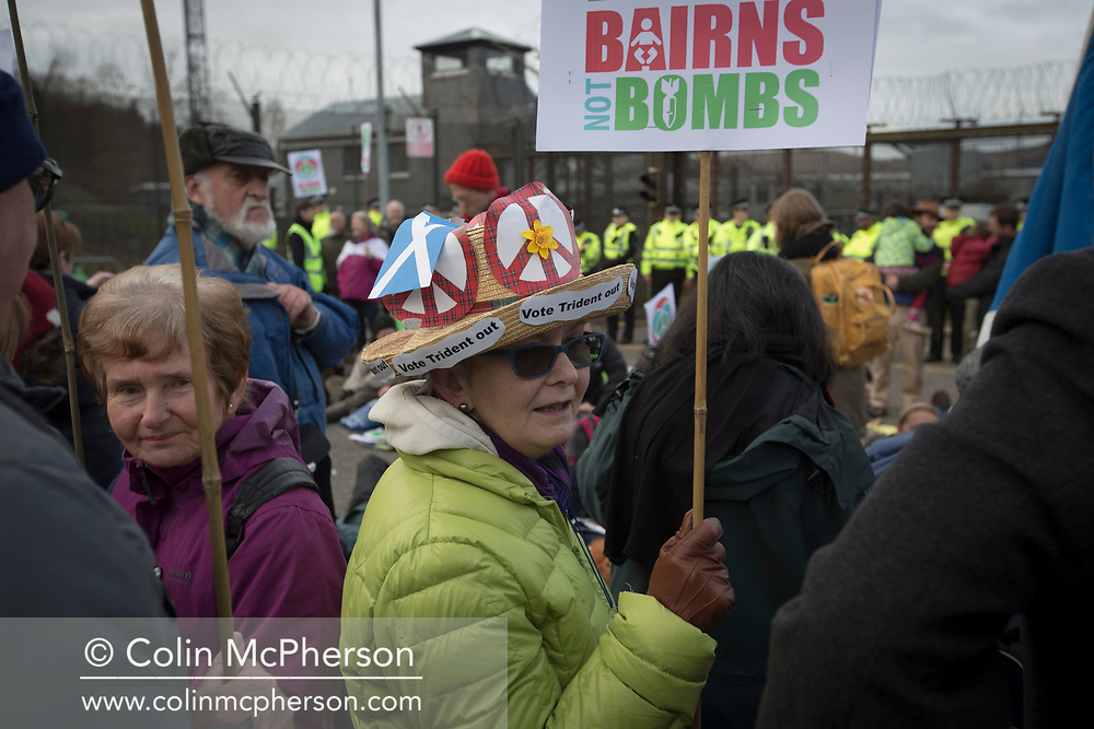 People holding placards in front of a line of police officers at the North Gate of Her Majesty's Naval Base, Clyde, Faslane, Scotland, during a blockade by around 150 people protesting against the Trident nuclear missile system. The protestors managed to shut down the base, preventing workers, contractors and naval personnel from accessing the site. A decision was due to be made by the UK government in 2016 whether to replace the Trident submarine system.