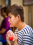 27 MARCH 2016 - BANGKOK, THAILAND: A young man prays with an Easter egg hanging off his finger during Easter services at Santa Cruz Church in Bangkok. Santa Cruz was one of the first Catholic churches established in Bangkok. It was built in the late 1700s by Portuguese soldiers allied with King Taksin the Great in his battles against the Burmese who invaded Thailand (then Siam). There are about 300,000 Catholics in Thailand, in 10 dioceses with 436 parishes. Easter marks the resurrection of Jesus after his crucifixion and is celebrated in Christian communities around the world.      PHOTO BY JACK KURTZ