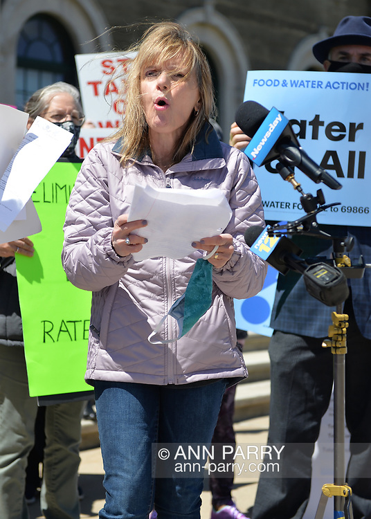 Mineola, New York, USA. April 26, 2021. AGATHA NADEL, Director of North Shore Concerned Citizens (NSCC) speaks at rally. Faced with a 26% rate increase from New York American Water going into effect May 1, 2021, activists and residents who are NYAW customers rally to urge NYS Assemby to push through legislation, before that date, corresponding with NYS Senate Bill S989A to establish a Nassau County Water Authority and except water works corporations in counties of populations over one million from a special franchise tax.
