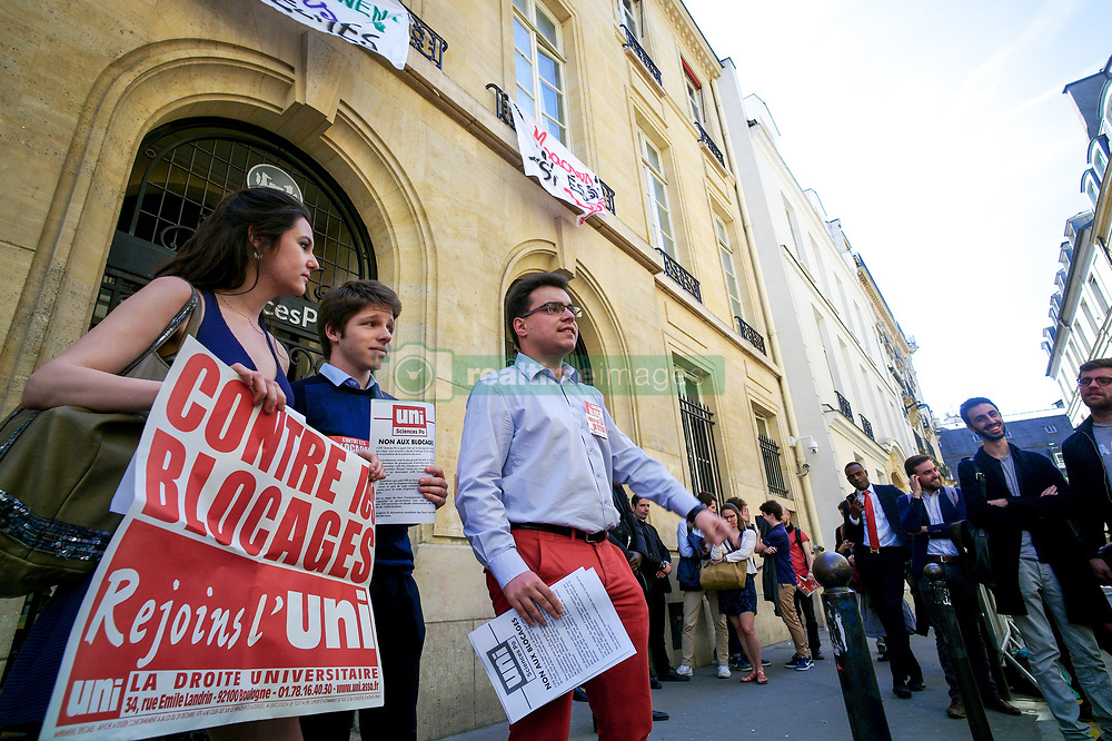 April 18, 2018 - Paris, Ile-de-France, France - Students from right-wing party hold signs reading 'against the blockings' as other students block the entrance of Sciences Po university on April 18, 2018 in Paris, as part of nation-wide demonstrations against higher education reforms, introduced by the French government that give public universities the power to set admission criteria and rank applicants. Placards, suspended from balconies of Sciences Po university, read (From L) ''Sciences Po's students against Macron's dictatorship'', ''Here are trained those who select. Blocking the elite factory.'' ''Macron your school is blocked' (Credit Image: © Michel Stoupak/NurPhoto via ZUMA Press)