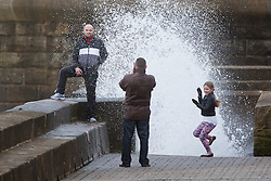 """© Licensed to London News Pictures. 09/11/2015. Bridlington, UK. FRAME 3 OF 9. A man poses for a photograph on the sea defences at the sea side town of Bridlington & gets caught out by a huge wave. The Yorkshire region was hit by severe gales this afternoon with winds up to 60mph. The Met Office warned West Yorkshire to expect gales and locally severe gales over high ground, with some """"very gusty"""" winds to the east of high ground as well.<br /> Photo credit: Andrew McCaren/LNP"""