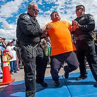 091413       Cable Hoover<br /> <br /> Gallup firefighter Nathaniel Brown, center, is helped to a mat by McKinley County Sheriff's officers Merlin Benally, right, and John Trevor-Smith as Brown receives a 50,000 volt shock during a taser demonstration at the Preparedness and Public Safety Day at the Rio West Mall in Gallup Saturday.