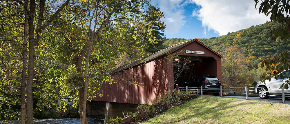 Automobiles drive through West Cornwall covered bridge over Housatonic River during The Fall in Connecticut, USA