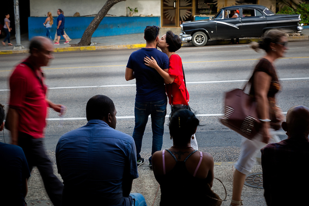 A couple waits for the bus together along La Rampa, a busy thoroughfare through the Vedado neighborhood of Havana.