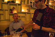 Wine Director Patrick Cappiello, in the plaid shirt, pouring for a customer.