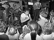 Christmas Party With Johnny Logan..1986..16.12.1986..12.16.1986..16th December 1986..At the 'Embankment',Tallaght, a charity Christmas Party was held for deprived children of the area. The main attraction was the singer and entertainer Johnny Logan,who with his band,entertained the children. Santa Claus took time off from his busy schedule to give a present to all the boys and girls. A great time was had by all...Johnny hunkers down to chat with the children gathered at the front of the stage.
