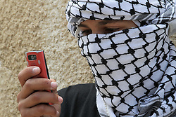 26.06.2015, Kfar Qaddum, PSE, Nahostkonflikt zwischen Israel und Palästina, im Bild ein vermummter Palästinenser mit Telefon // A masked Palestinian protester looks on his mobile during clashes with Israeli security forces following a demonstration against the expropriation of Palestinian land by Israel in the West Bank village of Kfar Qaddum, Palestine on 2015/06/26. EXPA Pictures © 2015, PhotoCredit: EXPA/ APAimages/ Ahmad Talat<br /> <br /> *****ATTENTION - for AUT, GER, SUI, ITA, POL, CRO, SRB only*****