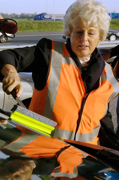 Nederland, Woerden, 1 nov 2005.Vanaf vandaag geldt op een aantal stukken snelweg langs steden een maximum snelheid van 80 km/uur. Dit om de luchtkwaliteit te verbeteren. Doordat bij 80 km per uur de doorstroming van het verkeer beter is, en omdat auto's , vooral diesel auto's, minder roet, fijn stof en uitlaatgassen zoals NO2 uitstoten is deze snelheidsbeperking ingesteld door minister Peijs van Verkeer. Als publiciteitsstuntje waste de minister vanmorgen autoramen bij een benzinestation langs de A12, vlak voor een stuk waar vanaf vandaag maar 80 gereden mag worden..mobiliteit, verkeer.Foto (c) Michiel Wijnbergh