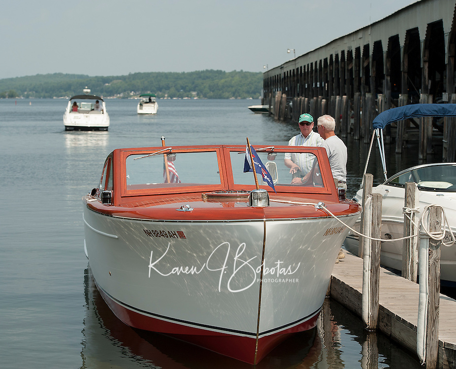 Gary Kiedaisch talks with Alan Lydiard after launching his fully restored 1952 27' Chris Craft Cruiser into Paugus Bay at Irwin Marine Friday afternoon.  (Karen Bobotas/for the Laconia Daily Sun)