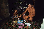 1991: Kenyah natives living in traditional longhouse, eating on the floor. Abu and his family. Long Geng, Belaga district, Sarawak, Borneo<br /> <br /> Tropical rainforest and one of the world's richest, oldest eco-systems, flora and fauna, under threat from development, logging and deforestation. Home to indigenous Dayak native tribal peoples, farming by slash and burn cultivation, fishing and hunting wild boar. Home to the Penan, traditional nomadic hunter-gatherers, of whom only one thousand survive, eating roots, and hunting wild animals with blowpipes. Animists, Christians, they still practice traditional medicine from herbs and plants. Native people have mounted protests and blockades against logging concessions, many have been arrested and imprisoned.