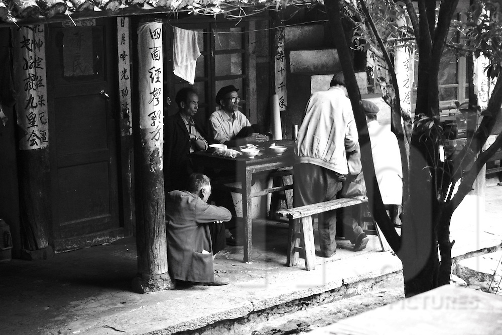 In a small pagoda with chinese writes a group of men is drinking tea. One man sit on the floor, his back against a pilar. An other man is smoking, wearing glasses and flat cap. Few bowls are on the wood table. One man is about to leave the place.