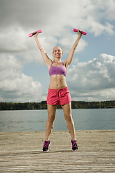 Woman training with dumbbells, Woerthsee, Bavaria, Germany