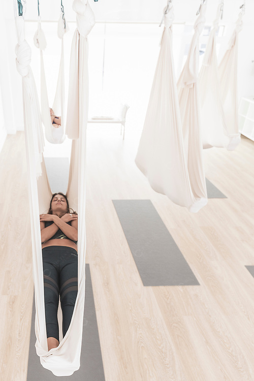 Aerial yoga class relaxation exercise inside hammock