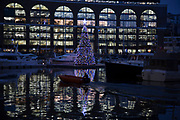 Christmas tree lit up at night with coloured lights on St Katherine Docks in London, England, United Kingdom. St Katharine Docks, in the London Borough of Tower Hamlets, were one of the commercial docks serving London, on the north side of the river. They were part of the Port of London, in the area now known as the Docklands, and are now a popular housing and leisure complex. Here it is now a central mooring for boats and yachts. (photo by Mike Kemp/In Pictures via Getty Images)