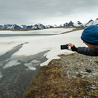 A Lindblad Expeditions guest takes a photo of Crean Lake with his smartphone. The Shackleton Hike leads from Fortuna Bay to Stromness on South Georgia Island.