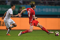 """Gareth Bale, right, of Wales national football team kicks the ball to make a pass against a player of Uruguay national football team in their final match during the 2018 Gree China Cup International Football Championship in Nanning city, south China's Guangxi Zhuang Autonomous Region, 26 March 2018.<br /> <br /> Edinson Cavani's goal in the second half helped Uruguay beat Wales to claim the title of the second edition of China Cup International Football Championship here on Monday (26 March 2018). """"It was a tough match. I'm very satisfied with the result and I think that we can even get better if we didn't suffer from jet lag or injuries. I think the result was very satisfactory,"""" said Uruguay coach Oscar Tabarez. Wales were buoyed by a 6-0 victory over China while Uruguay were fresh from a 2-0 win over the Czech Republic. Uruguay almost took a dream start just 3 minutes into the game as Luis Suarez's shot on Nahitan Nandez cross smacked the upright. Uruguay were dealt a blow on 8 minutes when Jose Gimenez was injured in a challenge and was replaced by Sebastian Coates. Inter Milan's midfielder Matias Vecino of Uruguay also fired at the edge of box from a looped pass but only saw his attempt whistle past the post. Suarez squandered a golden opportunity on 32 minutes when Ashley Williams's wayward backpass sent him clear, but the Barca hitman rattled the woodwork again with goalkeeper Wayne Hennessey well beaten."""