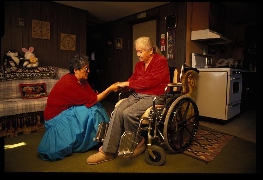 Sister Gloria Davis (left) prays with Rose Etsitty.  Chersihing tradition, the Catholic nun still attends Native American Church ceremonies.