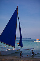 Boat with blue sail on White Sand Beach, Boracay, Philippines.