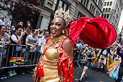 New York, NY - 30 June 2019. The New York City Heritage of Pride March filled Fifth Avenue for hours with participants from the LGBTQ community and it's supporters. A marcher wearing a red and gold dress, an elaborate tiara, and with a red cape flowing behind.