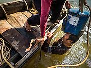 14 OCTOBER 2015 - BANGKOK, THAILAND:  A spotter helps the diver he works with surface from the bottom of the Chao Phraya River in Bangkok. Divers work in two man teams on small boats in the Chao Phraya River. One person stays in the boat while the diver scours the river bottom for anything that can be salvaged and resold. The divers usually work close to shore because the center of the river is a busy commercial waterway with passenger boats and commercial freight barges passing up and down the river all day long. The Chao Phraya is a dangerous river to dive in. It's deep, has large tidal fluctuations, is fast flowing and badly polluted. The divers make money only when they sell something.   PHOTO BY JACK KURTZ