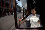 Waitress cleans the windows of a Chinese restaurant in an area just south of Tiananmen in the Xuanwu district in Beijing, China. This is a shopping street in a traditional sense.