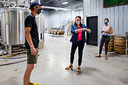 """22 JULY 2020 - AMES, IOWA: ELLIOT THOMPSON, owner of Alluvial Brewing, left, talks to THERESA GREENFIELD, center, about the needs of small businesses during a visit by Greenfield to Alluvial Brewing in Ames, IA. Greenfield, a Democrat, is running for the US Senate against incumbent Republican Senator Joni Ernst. Recent polls have Greenfield slightly ahead of or statistically tied with Ernst, who is closely allied with President Donald Trump. Although Greenfield is not doing much in person campaigning with big events, she is meeting with business people across the state of Iowa to promote her """"Small Towns, Bigger Paychecks"""" economic program.       PHOTO BY JACK KURTZ"""