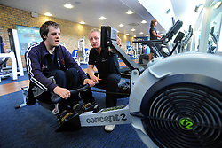 A young man works out on the rowing machine in a gym; helped by a sports instructor as part of a Sport Ability Day North Yorkshire,
