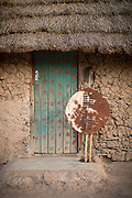 Village hut entrance and thatched roof showing traditional warrior's shield and spear, Eswatini