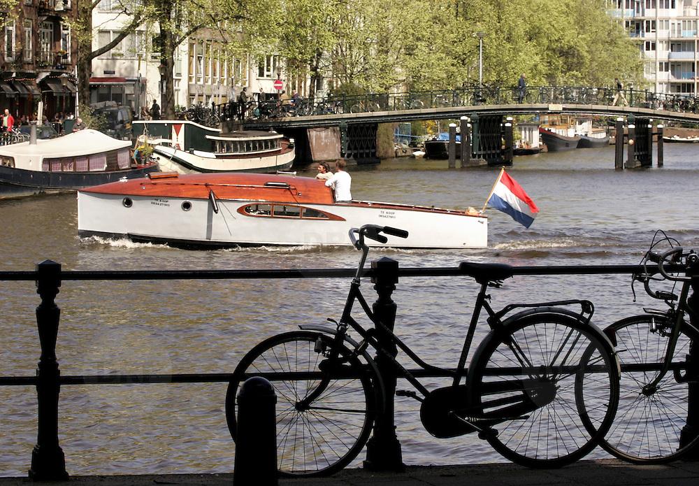 Nederland Amsterdam 26 april 2006 20060426 .Stadgezicht Amsterdam fietsen met op de achtergrond een sloep in de grachten ..Foto David Rozing
