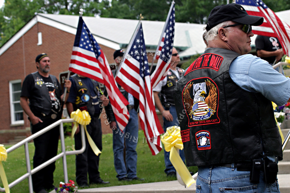 Members of the Patriot Guard Riders are lined up while holding US flags during the funeral service of Sgt. Ian T. Sanchez, in Staten Island, NY., on Tuesday, June 27, 2006. Sgt. Sanchez, a 26-year-old American serviceman was killed by a roadside bomb in the Pech River Valley, Afghanistan. The Patriot Guard Riders is a diverse amalgamation of riders from across the United States of America. Besides a passion for motorcycling, they all have in common an unwavering respect for those who risk their lives for the country's freedom and security. They are an American patriotic group, mainly but not only, composed by veterans from all over the United States. They work in unison, calling upon tens of different motorcycle groups, connected by an internet-based web where each of them can find out where and when a 'Mission' is called upon, and have the chance to take part. This way, the Patriot Guard Riders can cover the whole of the United States without having to ride from town to town but, by organising into different State Groups, each with its own State Captain, they are still able to maintain strictly firm guidelines, and to honour the same basic principles that moves the group from the its inception. The main aim of the Patriot Guard Riders is to attend the funeral services of fallen American servicemen, defined as 'Heroes' by the group,  as invited guests of the family. These so-called 'Missions' they undertake have two basic objectives in particular: to show their sincere respect for the US 'Fallen Heroes', their families, and their communities, and to shield the mourners from interruptions created by any group of protestors. Additionally the Patriot Guard Riders provide support to the veteran community and their families, in collaboration with the other veteran service organizations already working in the field.   **ITALY OUT**