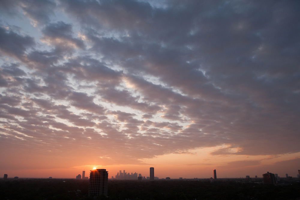 Houston, Texas silhouetted skyline with beautiful sunrise and cloud formations.