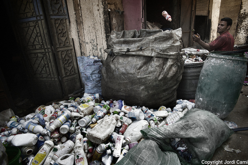 """Classification of different types of plastic in Mokattam.The quarry was originally located where the settlement of Mokattam, is now used for storage of paper and aluminum.On the outskirts of Cairo in the middle of Manshiet Nasr neighborhood is located Mokattam settlement known as """"Garbage City"""" is inhabited by Zabbaleen, a community of about 45,000 Coptic Christians living for decades to recycle waste generated by the Egyptian capital: plastic, aluminum, paper and organic waste transformed into compost. Most part of the Association for the Protection of the Environment (APE), an NGO that works in the area, whose objectives are to protect the environment and improve the livelihoods of garbage scavengers in Cairo. According to the UN, the work is done in Mokattam is one of the ten best examples of world environmental improvement. El Cairo , Egypt, June 2011. ( Photo by  Jordi Camí )."""
