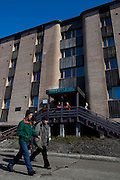 Miners walk past the Barentsburg hotel, while tourists look on. Barentsburg is a Russian coal mining town in the Norwegian Archipelego of Svalbard. Once home to about 2000 miners and their families, less than 500 people now live here.
