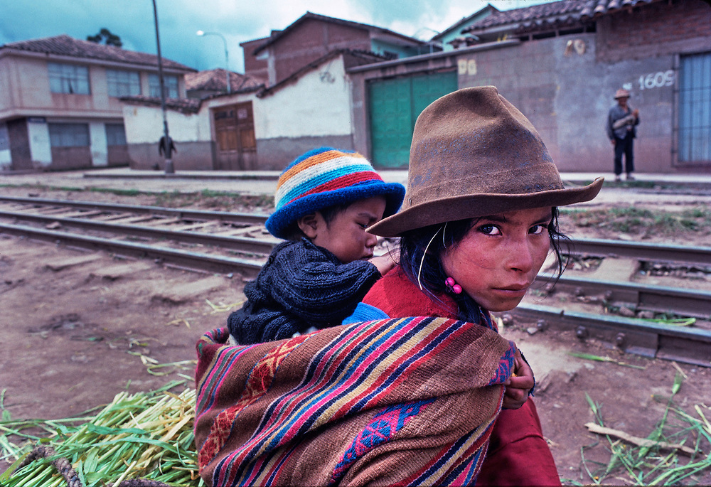 Indigenous girl carries her baby brother slung over her back, Cuzco, Peru