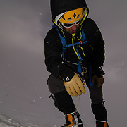 David Morton rests in the midst of a storm as he makes his way up the West Ridge Headwall on Mount Everest, Nepal.
