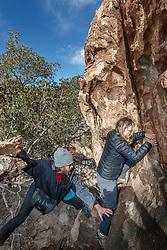 Sarah Hepola and guide Jacob Garza crossing narrow ledge at Hueco Tanks State Park & Historic Site, El Paso, Texas. USA.
