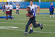 Middletown, New York - A boy runs with the football as a Middletown High School football player chases him during a drill at Faller Stadium during Family Fun Night on May 17, 2013.