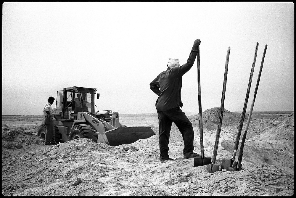 Workers dig up the mass graves near Al-Musayab, Iraq, with a bulldozer and shovels. The team leader at the site took care to avoid destroying the bodies with the bulldozer, unlike at other sites in Iraq.