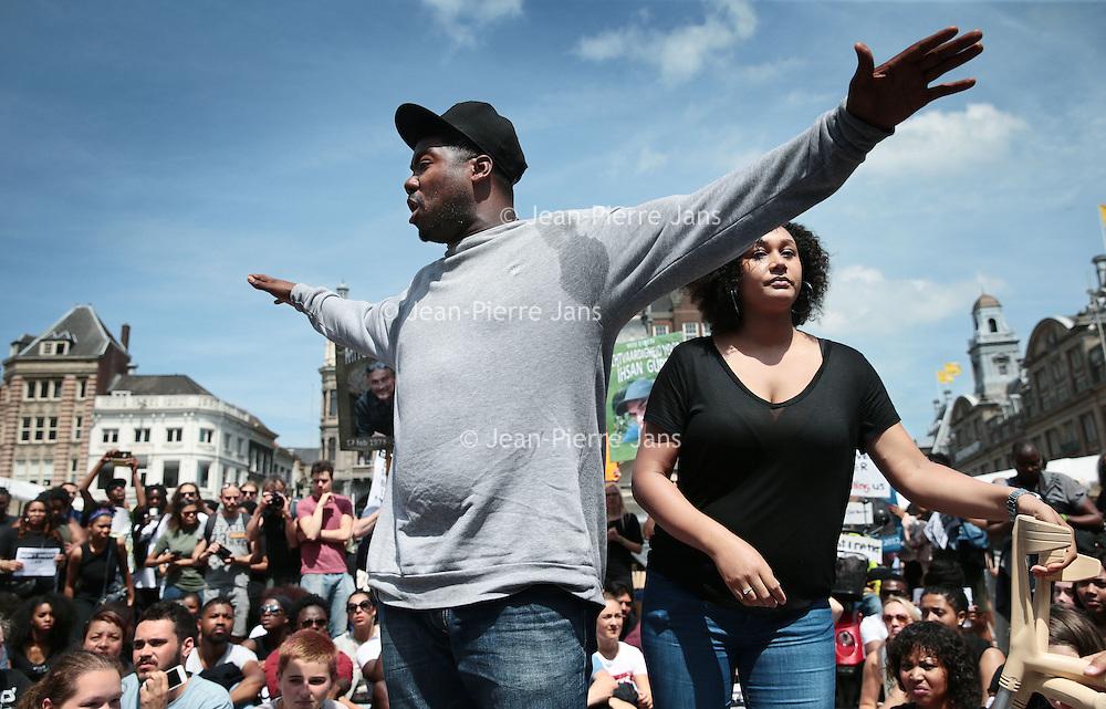 """Nederland, Amsterdam, 10 juli 2016<br /> Een paar honderd mensen zijn vanmiddag op de Dam in Amsterdam bijeen gekomen om in stilte te protesteren tegen het politiegeweld in Amerika. Onder de naam Black Lives Matter trok de stoet vervolgens door de stad.<br /> """"Mijn initiatief was om alleen op de Dam te gaan staan met een papiertje op mijn rug"""", vertelt initiatiefneemster Anna Hammond.""""Eniedereen die langs komt kon dan vragen aan mij stellen, en ik zou die vragen dan beantwoorden.""""<br /> """"Ik heb dat op mijn Facebook gepost, omdat ik dacht: ja misschien willen wel wat vrienden meedoen. En dat is viral gegaan. Ik had nooit gedacht dat er zo veel mensen op af zouden komen"""",zegt ze verrast.<br /> Op de foto: rapper Gikkels (Gideon Everduin) spreekt de menigte toe.<br /> rechts in beeld initiatiefneemster Anna Hammond.<br /> <br /> Netherlands, Amsterdam, July 10, 2016<br /> A few hundred people met this afternoon on the Dam in Amsterdam to protest silently against police violence in America. Under the name Black Lives Matter the procession continued through the city.""""My initiative was to just stand on the Dam with a piece of paper on my back,"""" says initiator Anna Hammond. """"And everyone who comes along could then ask me questions, and I would answer those questions.""""I've posted on my Facebook, because I thought, yeah maybe do want to join some friends and that went viral. I never thought that so many people would join,"""" She says surprised.<br /> In the photo: rapper Gikkels (Gideon Ever Dune) speaks to the crowd.right image initiator Anna Hammond.<br /> <br /> Foto: Jean-Pierre Jans"""