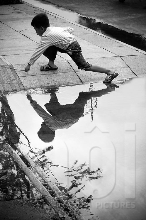 A vietnamese kid is playing in the street after rain close to a puddle. Region Nha Trang, Khanh Hoa area, Viet Nam, Asian.