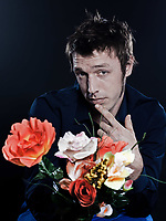 studio portrait on black background of a funny expressive caucasian man offering flowers shy