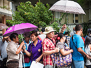 21 JULY 2015 - BANGKOK, THAILAND: People at a protest of blind people wait out a passing rain shower under umbrellas. About 50 blind people held a protest at the National Counter Corruption Commission offices Phitsanulok Road in Bangkok, across the street from Government House, Tuesday. Many blind and vision impaired people in Thailand sell lottery tickets and members of the blind community have been upset about changed in lottery ticket policies.     PHOTO BY JACK KURTZ