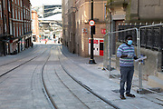 Man weraing a surgical face mask in virtually deserted streets looking down tram lines towards the exterior of Grand Central on 24th April 2020 in Birmingham, England, United Kingdom. Coronavirus or Covid-19 is a new respiratory illness that has not previously been seen in humans. While much or Europe has been placed into lockdown, the UK government has extended stringent rules as part of their long term strategy, and in particular social distancing.