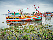 "23 JUNE 2015 - MAHACHAI, SAMUT SAKHON, THAILAND: The fishing boat carrying the City Pillar Shrine up the Tha Chin (Chin River) in Mahachai. The Chaopho Lak Mueang Procession (City Pillar Shrine Procession) is a religious festival that takes place in June in front of city hall in Mahachai. The ""Chaopho Lak Mueang"" is  placed on a fishing boat and taken across the Tha Chin River from Talat Maha Chai to Tha Chalom in the area of Wat Suwannaram and then paraded through the community before returning to the temple in Mahachai.   PHOTO BY JACK KURTZ"